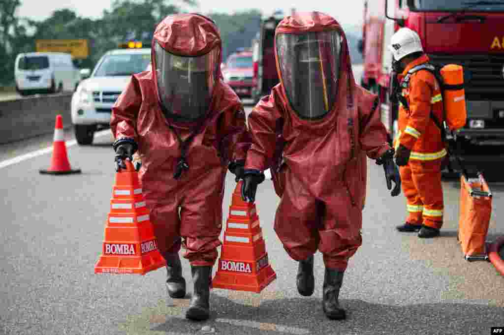 Members of a Malaysian hazardous disaster emergency response team wearing protective suits take part in a trasportation emergency response drill 'Ex-Eagle' on a highway near Bentong, outside Kuala Lumpur.