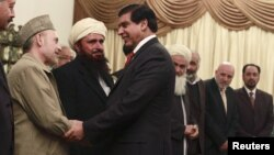 Pakistan's Prime Minister Raja Pervez Ashraf (R) shakes hands with members of Afghanistan's High Peace Council at the prime minister's residence in Islamabad, November 12, 2012.