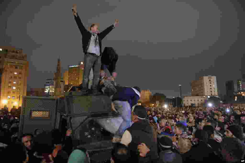Protesters celebrate the capture of a state security armored vehicle that demonstrators commandeered during clashes with security forces and brought to nearby Tahrir Square in Cairo, Egypt, January 28, 2013.