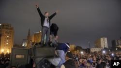 埃及的示威者星期一在開羅解放廣場附近慶祝繳獲政府的國家安全裝甲車輛