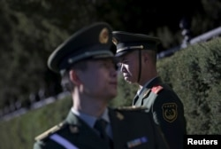 FILE - Paramilitary police officers stand guard for a welcoming ceremony for Germany's Chancellor Angela Merkel outside the Great Hall of the People in Beijing, China. A new report from Amnesty International alleges Chinese police widely use torture.