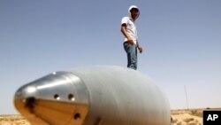 图为一名反卡扎菲战士9月8日站立在一颗导弹上