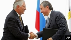 FILE - Igor Sechin, CEO of state-controlled Russian oil company Rosneft, right, and Exxon Mobil Corp. CEO Rex Tillerson shake hands after signing an agreement at the Black Sea port of Tuapse, southern Russia, June 15, 2012.