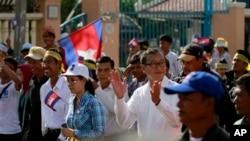 ကေမၻာဒီးယားအတုိက္အခံေခါင္းေဆာင္ Sam Rainsy (လယ္) ႏွင့္ သူ႔အားေထာက္ခံသူမ်ား ၿမိဳ႕ေတာ္ ဖႏြမ္းပင္မွာ ဆႏၵျပေနစဥ္။ (စက္တင္ဘာ ၁၅၊ ၂၀၁၃)