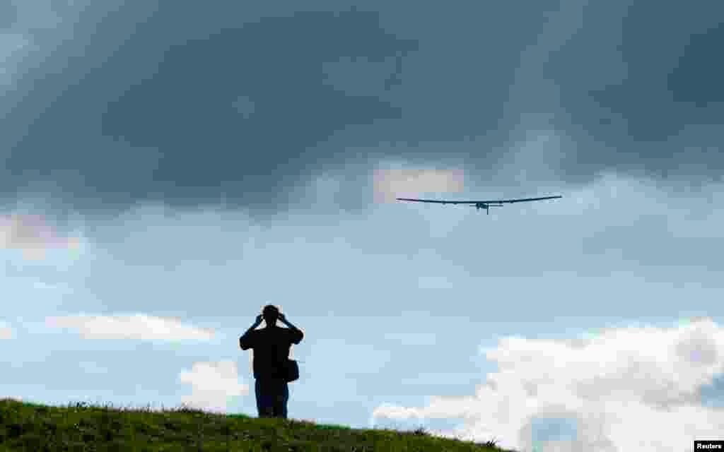 Seorang pria menonton uji terbang pesawat bertenaga surya, 'Impulse 2' di Payerne, Swiss. Pesawat Impulse 2 memiliki berat 2,4 ton dengan rentangan sayap sepanjang 72 meter, yang dilengkapi dengan 17.000 sel-sel surya.