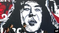 北京街头的学雷锋宣传画。几个行人从画前走过 (2003年)资料照片