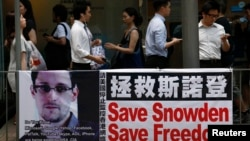 People carrying mobile phones walk past a banner supporting Edward Snowden, a former contractor at the National Security Agency (NSA), at Hong Kong's financial Central district, June 18, 2013.
