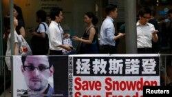 Des passants accrochés à leurs téléphones portables se succédant devant une banderole en soutien à Edward Snowden, ex-consultant de la National Security Agency (NSA), dans le centre financier de Hong Kong, 18 juin 2013.