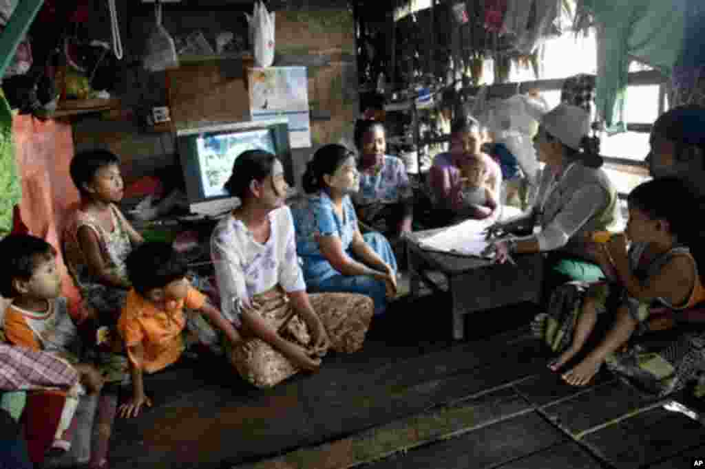 A Myanmar census enumerator asks questions to a family member while collecting information in Dala township Sunday, March 30, 2014, in Yangon, Myanmar. Enumerators fanned out across Myanmar on Sunday for a census that has been widely criticized for stoki
