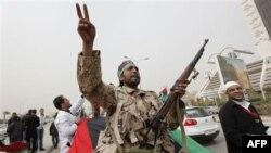 Naoružani libijski pobunjenici skandiraju parole protiv Gadafija na protestnom mitingu u Bengaziju.