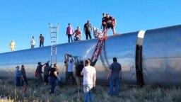 Pada foto yang dirilis oleh Kimberly Fossen ini, tampak orang orang berada di lokasi kejadian di mana kereta api Amtrak train tergelincir pada Sabtu (25/9) lalu. Lokasi tergelincirnya kereta api berada di wilayah utara Montana. (Foto: Kimberly Fossen via AP)