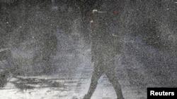 2014年1月6日,在伊利诺伊州芝加哥市,一位女士冒着刺骨的寒风走上街头,冷风迎面吹来,扬起积雪,遮挡住视线。
