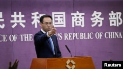 FILE - Chinese Ministry of Commerce spokesman Gao Feng gestures as journalists raise hands for questions during a press conference at the Ministry of Commerce in Beijing, April 6, 2018.