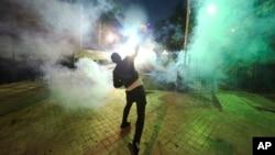 Demonstrant baca baklju ka pripadnicima albanske policije, na antivladinim demonstracijama u Tirani, Albanija, 8. juna 2019.