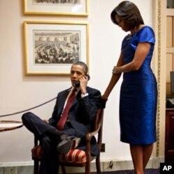 ປະທານາທິບໍດີ ໂອບາມາ ກັບພັນລະຍາ ທ່ານນາງມີແຊລ ໂອບາມາ ໂທລະສັບໄປສະແດງຄວາມດີໃຈ ກັບພໍ່ຂອງນາງ Jessica Buchanan ຢູ່ທໍານຽບຂາວ ຫລັງຈາກກ່າວຄໍາປາໄສຕໍ່ລັດຖະສະພາ, ຄືນວັນອັງຄານ ທີ 24 ມັງກອນ 2012. (AP Photo/Pete Souza, White House)