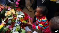 Một bé gái đặt bó hoa bên ngoài bệnh viện ở Pretoria, Nam Phi nơi cựu tổng thống Nelson Mandela đang được điều trị 27/6/13