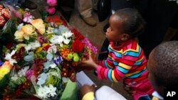 An unidentified young girl lays flowers outside the Mediclinic Heart Hospital where former South African President Nelson Mandela is being treated in Pretoria, June 27, 2013.