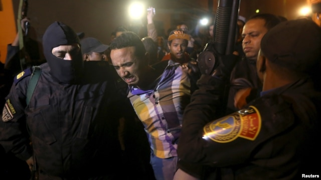 Security forces detain a man at the scene of a bomb blast in a main street in Giza, Egypt, Jan. 21, 2016.