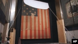 "In this Nov. 20, 1998 file photo, workers at the Smithsonian's National Museum of American History cover the flag that inspired ""The Star Spangled Banner,"" prior to the flag's restoration."