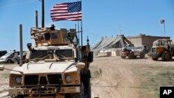 Seorang tentara AS (kiri, duduk di atas kendaraan lapis baja di Manbij, Suriah utara, Rabu, April 4, 2018. (Foto: dok).