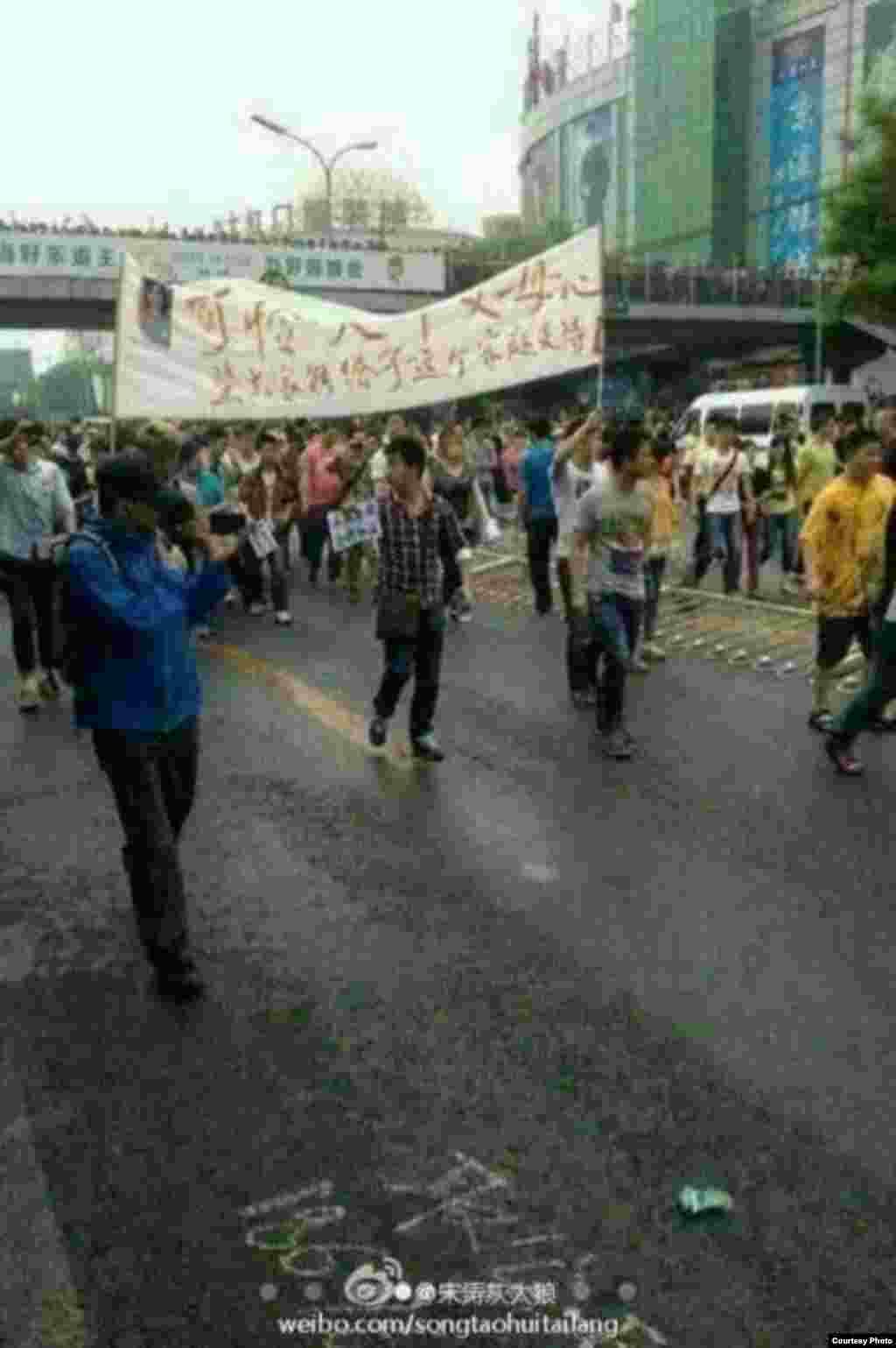 群众拉开抗议的标语在大街上游行(网民提供)