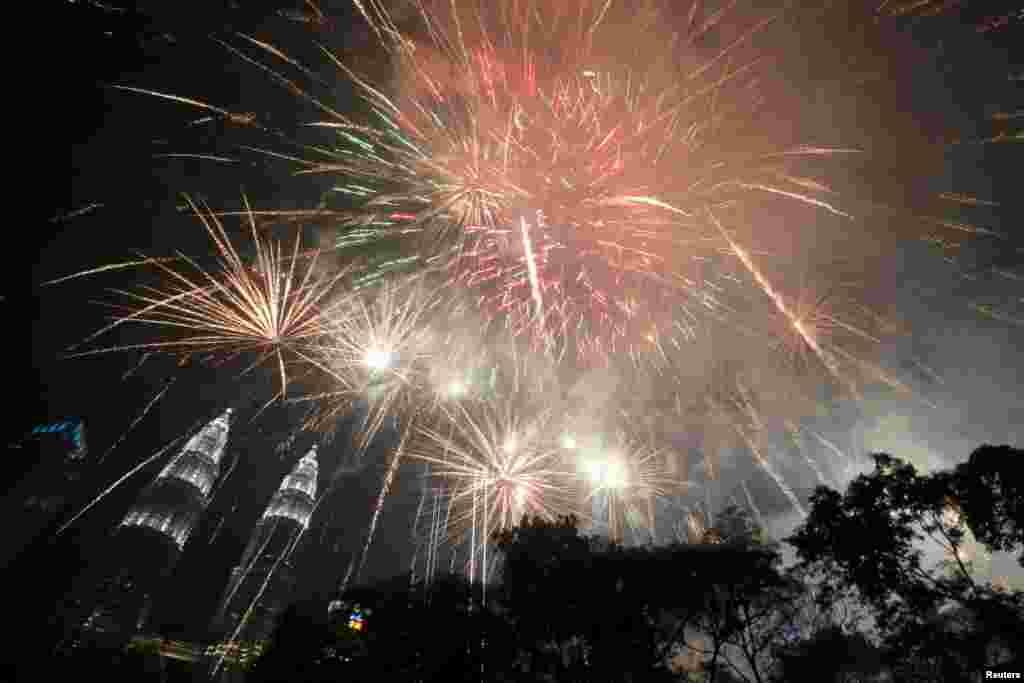 Fireworks explode near Petronas Twin Towers during New Year celebrations in Kuala Lumpur, Malaysia, Jan. 1, 2019.