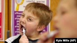 David Taylor (9 tahun), mulai menyikat giginya setelah makan siang di Moscow, Idaho. Ini adalah bagian dari program yang dimulai oleh Dokter Gigi Rich Bailey untuk membantu mempromosikan kesehatan gigi, 12 Maret 2010. (Foto: AP/Kyle Mills)