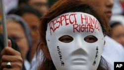 "Seorang demonstran menggunakan topeng bertuliskan pesan ""Hormati HAM"" di Manila untuk memperingati Hari HAM di Filipina, Minggu, 10 Desember 2017."