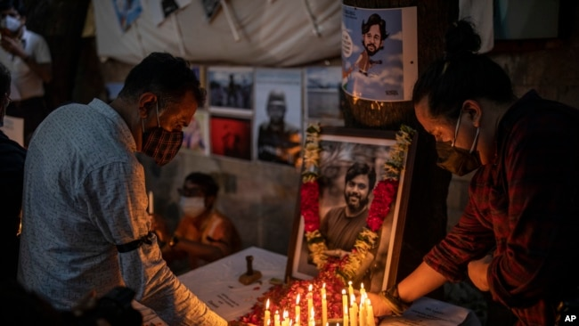 Journalists light candles and pay tribute to Reuters photographer Danish Siddiqui in New Delhi, India, Saturday, July 17, 2021.