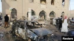 Des gens passent l'épave d'une voiture bombardée à l'extérieur du Musée de Raqqa, après des frappes aériennes que les défenseurs des droits de l'homme attribuent aux forces fidèles au président Bachar al-Assad de la Syrie à Raqqa, Est de la Syrie, contrôlé par l'Etat islamique, le 25 novembre 2014.