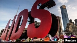 FILE - Flowers are laid as tributes to those killed in the Malaysia Airlines flight MH17, at the base of a large sign for the 20th International AIDS Conference in Melbourne, Australia, July 20, 2014.