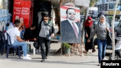 People walk next to a poster depicting Lebanon's Prime Minister Saad al-Hariri, who has resigned from his post, along a street in the mainly Sunni Beirut neighborhood of Tariq al-Jadideh in Beirut, Lebanon, Nov. 6, 2017.