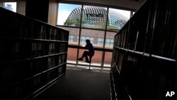 FILE - A man is silhouetted at a library in Singapore.