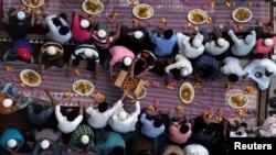 Ilustrasi. Muslim membagikan makanan saat mereka menunggu untuk berbuka puasa di luar masjid selama bulan suci Ramadhan, di Manama, Bahrain. (Foto: Reuters/Hamad I Mohammed)