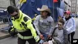 2013年4月15日,连环爆炸发生后,医疗急救人员把一名受伤男子抬过波士顿马拉松赛的终点线。