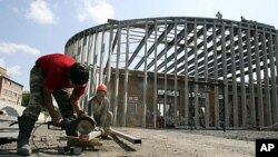 Workers build a monument around a building at School Number One in the North Ossetian town of Beslan August 18, 2011 (file photo)