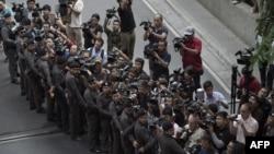 媒体站在警戒线后拍摄曼谷爆炸案嫌疑人被带下警车指认现场的情景(2015年9月9日)