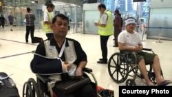 Cambodian opposition​ CNRP lawmakers Nhay Chamroeun (left) and Kong Saphea (right) are seen arriving in wheelchairs at a Bangkok airport on Tuesday, October 27, 2015, after being beaten by protesters in Phnom Penh, Cambodia. (Photo courtesy of Nhay Chamroeun)
