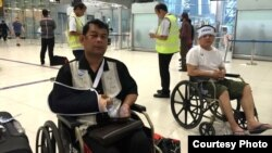 Cambodian opposition CNRP lawmakers Nhay Chamroeun (left) and Kong Saphea (right) are seen arriving in wheelchairs at a Bangkok airport on Tuesday, October 27, 2015 after being beaten by protesters in Phnom Penh, Cambodia on Monday. (Courtesy of Nhay Chamroeun)