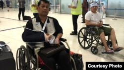 Cambodian opposition CNRP lawmakers Nhay Chamroeun (left) and Kong Saphea (right) are seen arriving in wheelchairs at a Bangkok airport on Tuesday, October 27, 2015 after being beaten by protesters in Phnom Penh, Cambodia on Monday. (Courtesy of Nhay Cha