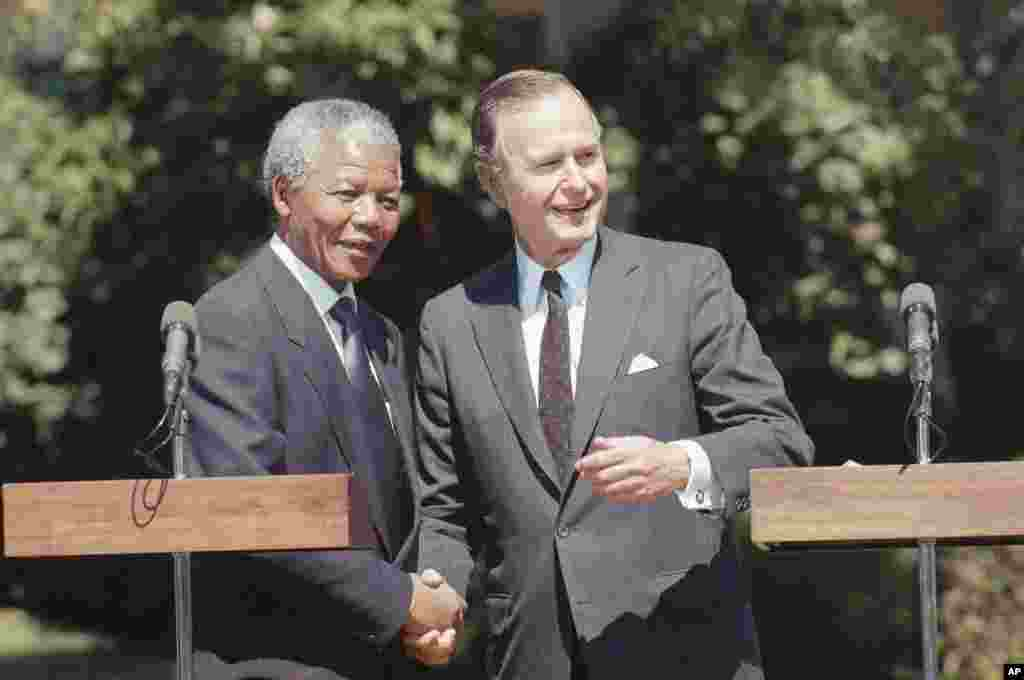 This June 25, 1990 photo shows then President George H. W. Bush greeting then African National Congress Deputy President Nelson Mandela at the White House.