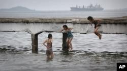 지난 6월 북한 원산 해변의 잔교에서 어린 소녀들이 물 속으로 뛰어들고 있다.