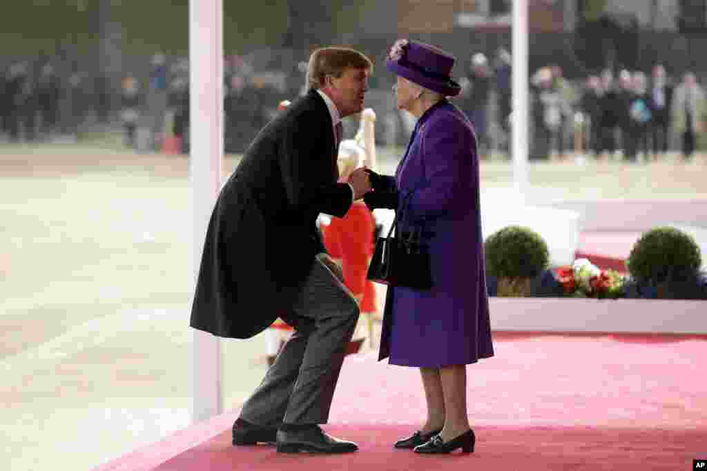Netherlands' King Willem-Alexander bends down to kiss Britain's Queen Elizabeth II as she greets him upon his arrival during a Ceremonial Welcome on Horse Guards Parade in London, Oct. 23, 2018.