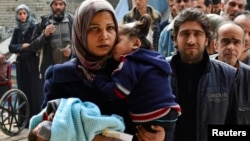 FILE - Residents line up to receive humanitarian aid at the Palestinian refugee camp of Yarmouk, in Damascus, Syria, March 2015.