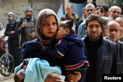FILE - Residents line up to receive humanitarian aid at the Palestinian refugee camp of Yarmouk, in Damascus, Syria, March 11, 2015.