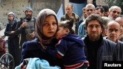 دمشق میں یرموک فلسطینی کمیپ میں مقیم افراد امداد لینے کے لیے قطار میں کھڑے ہیں۔ فائل فوٹو