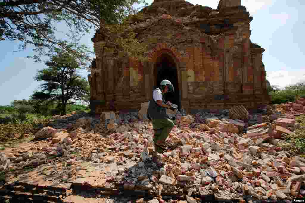 A photographer walks outside a collapsed pagoda after an earthquake in Bagan, Myanmar.