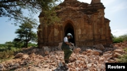 FILE - A photographer walks outside a collapsed pagoda after an earthquake in Bagan, Myanmar, Aug. 25, 2016.