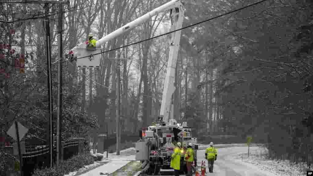 Les employés de Duke Energy, une campagne électrique, travaillent pour rétablir le courant dans un quartier à Matthews, Caroline du Nord, 22 janvier 2016. Une tempête de neige massive a commencé à tomber sur le sud et l'est des États-Unis avec des annulations de vols de masse, cinq Etats déclarant l'état d'urgence et plus de 2 pieds (60 centimètres) prédit pour Washington seul.