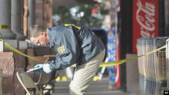An FBI agent writes down information as he looks at a chair and the ground where Rep. Gabrielle Giffords was shot at a local Safeway in Tucson, Arizona, 10 Jan 2011